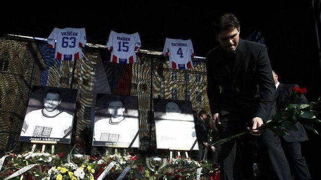 Jaromír Jágr pokládá květinu při pietním aktu na Staroměstském náměstí, kde se lidé lučili se zesnulými hokejisty.
