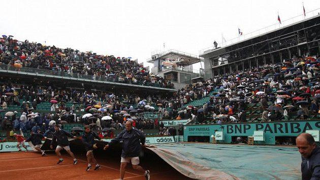 Pracovníci roztahují plachtu na kurtech Roland Garros