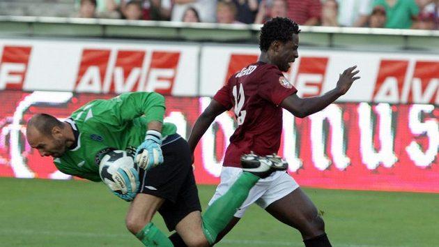 Před dotírajícím sparťanským útočníkem Bony Wilfriedem sbírá míč brankář Mladé Boleslavi Michal Vorel.