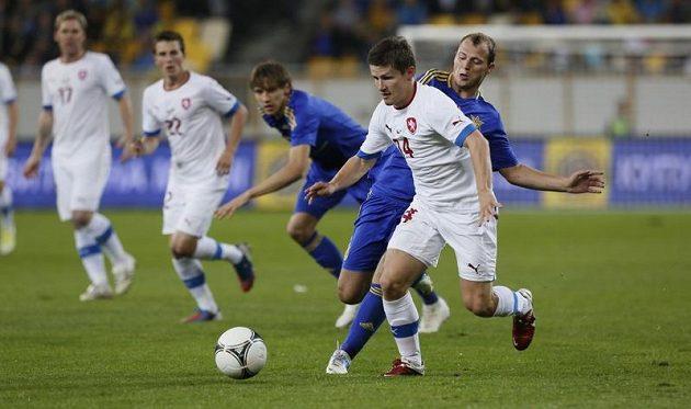 Václav Pilař (v bílém) se snaží udržet míč před dotírajícím soupeřem z Ukrajiny.