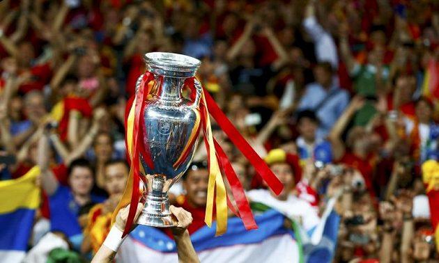 Ruce španělského forvarda Fernanda Torrese třímají pohár mistrů Evropy.