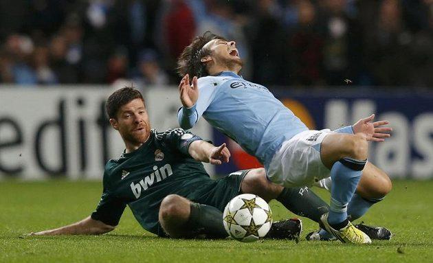 Zákrok Xabiho Alonsa z Realu Madrid (vlevo) Davida Silvu z Manchesteru City asi bolel. Ale ještě víc mohou Citizens litovat ztracených nadějí na postup do vyřazovacích bojů Ligy mistrů