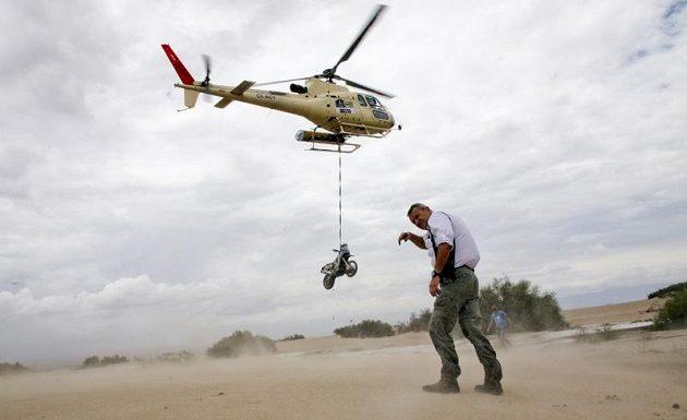 Ředitel Rallye Dakar Etienne Lavigne se kryje před prachem, který rozvířila helikoptéra odvážející motocykl Herva Thierryho z Francie.