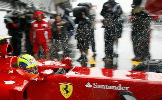 Kapky vody odletující od kol monopostu Ferrari Felipeho Massy.
