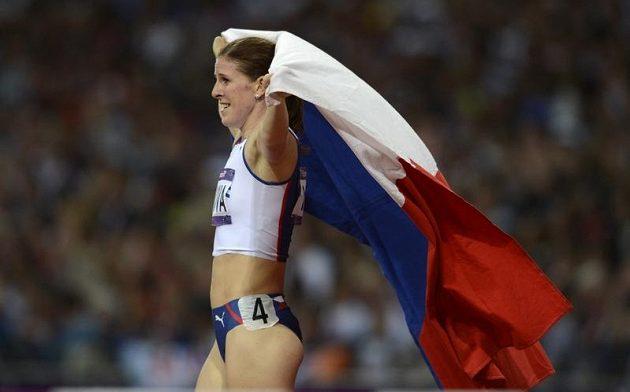 Zuzana Hejnová se raduje s českou vlajkou po zisku bronzové olympijské medaile na trati 400 metrů překážek.