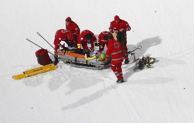 Ruský skokan na lyžích Denis Kornilov (na nosítkách) v péči lékařů po těžkém pádu v kvalifikaci na závod v Bischofshofenu.