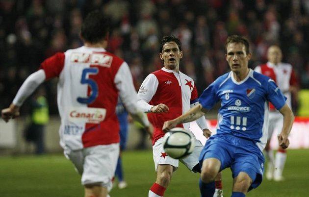 Obránce Slavie Milan Nitrianský a ostravský Lukáš Droppa bojují o míč. Uprostřed přihlíží Karol Kisel.