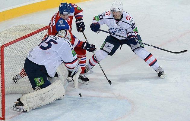 Mathias Porseland z týmu Lev Praha se snaží zasunout puk za záda brankáře Novosibirsku Jeffa Glase.