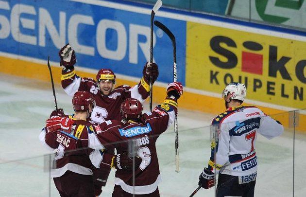 Hokejisté Sparty (zleva) Jiří Sekáč, Marek Hovorka a Michal Broš se radují z branky do pardubické sítě.