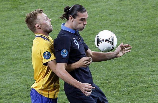 Útočník Anglie Andy Carroll si kryje míč před Sebaastianem Larssonem ze Švédska.