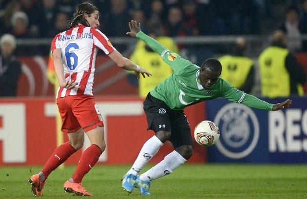 Didier Ya Konan (vpravo) z Hannoveru se snaží odpoutat od Luise Filipa z Atletika Madrid.