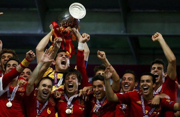 Třetí vítězství na velkém turnaji v řadě! Brankář Španělska Iker Casillas třímá pohár a bouřlivě oslavuje se spoluhráči úspěšnou obhajobu na mistrovství Evropy.