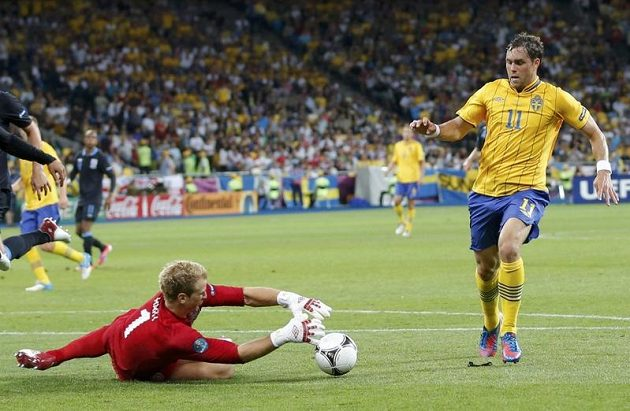 Brankář Anglie Joe Hart zasahuje před Švédem Johanem Elmanderem.