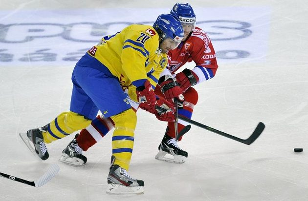 Český zadák Marek Židlický (vpravo) v souboji s Joelem Lundqvistem ze Švédska.