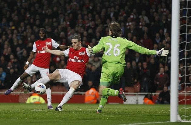 Thomas Vermaelen z Arsenalu (uprostřed) překonává gólmana Newcastlu Tima Krula.