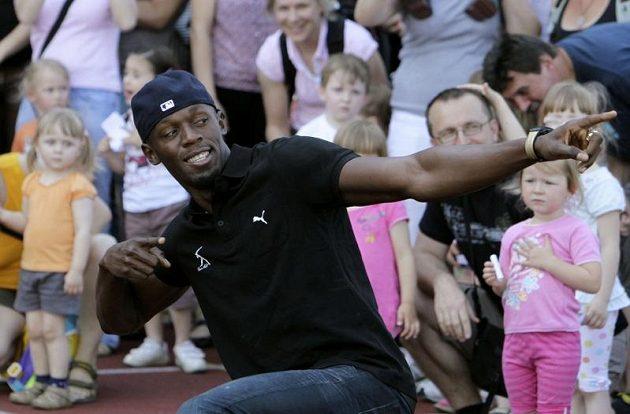 Jamajský sprinter Usain Bolt předvádí dětem v Ostravě své typické vítězné gesto před startem na Zlaté tretře.