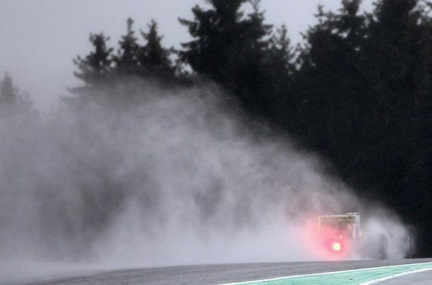 Oblak vodní tříště za monopostem Ferrari Fernanda Alonsa.