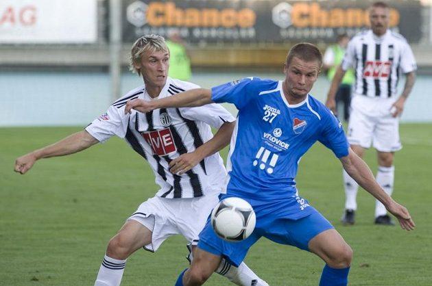 Dominik Kraut z Baníku Ostrava (vpravo) kryje míč před českobudějovickým Pavlem Novákem.