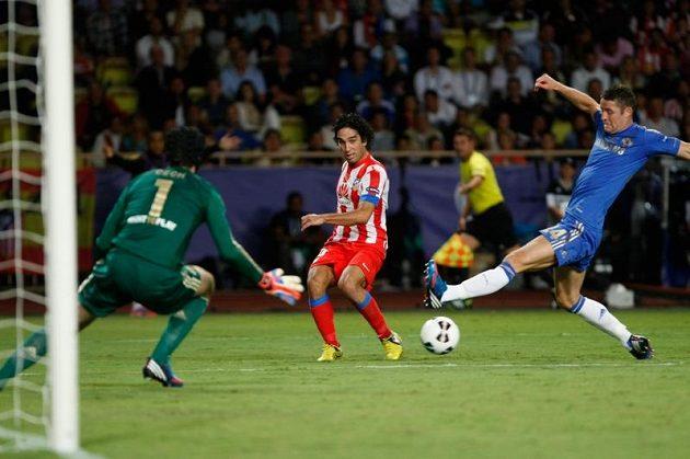 Obránce Chelsea Gary Cahill (vpravo) se marně snaží zblokovat střelu Ardy Turana z Atlétika Madrid, míč se chystá zlikvidovat brankář Petr Čech.