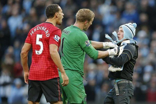 Fanouška Manchesteru City drží brankář Citizens Joe Hart (uprostřed). Vlevo obránce Manchesteru United Rio Ferdinand.