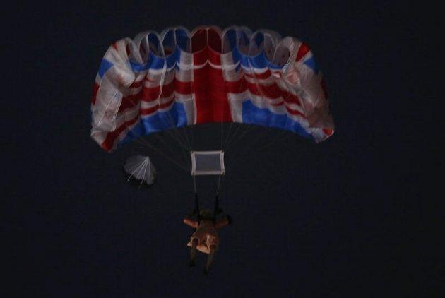 Herec v přestrojení za britskou královnu Alžbětu na padáku nad olympijským stadiónem během zahajovacího ceremoniálu.