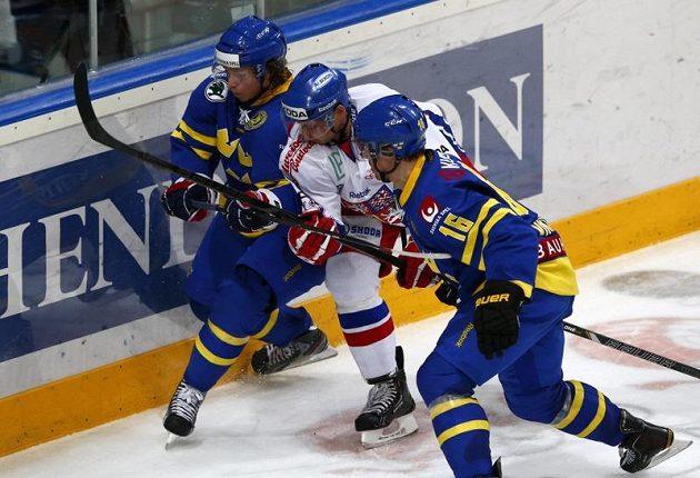 Jakub Orsava se snaží projít mezi švédským dvojblokem Nicklas Bäckström (vlevo), Tobias Viklund