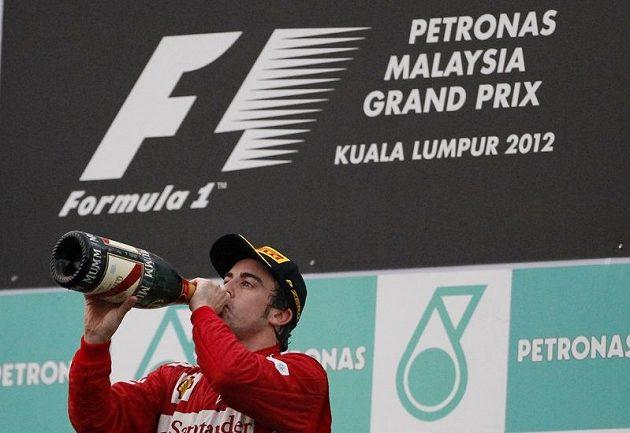 Španěl Fernando Alonso pije vítězné šampaňské p Velké ceně Malajsie.