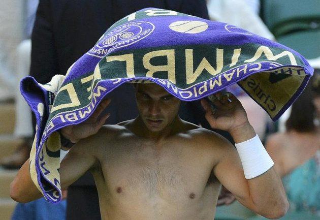 Rafael Nadal se ukrývá před diváky ručníkem.
