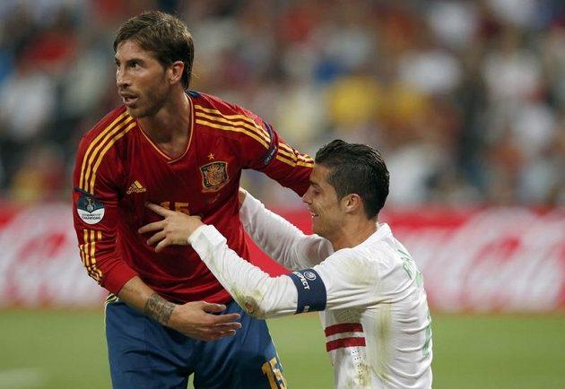 Španělský bek Sergio Ramos pomáhá na nohy klubovému parťákovi z Realu Madrid Cristianu Ronaldovi