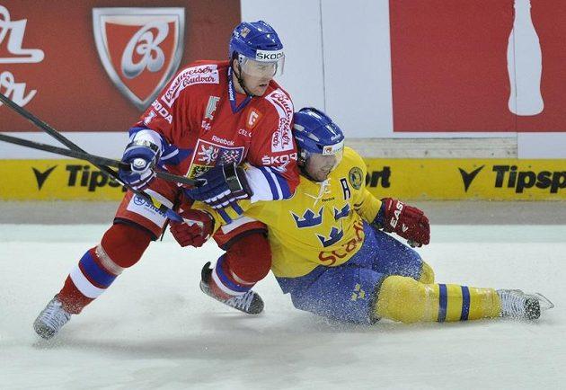 Český bek Marek Židlický (vlevo) bojuje s Joëlem Lundqvistem ze Švédska.