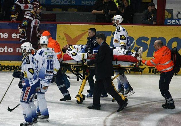 Zraněný obránce Brna Milan Hruška opouští ledovou plochu na nosítkách.