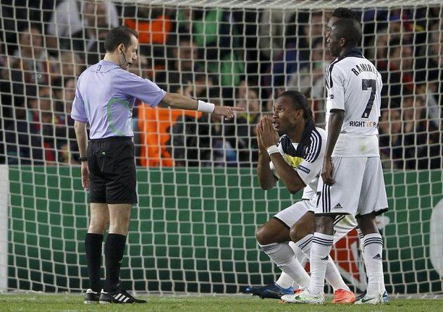 Didier Drogba se sepnutýma rukama před rozhodčím, který nařídil penaltu proti Chelsea