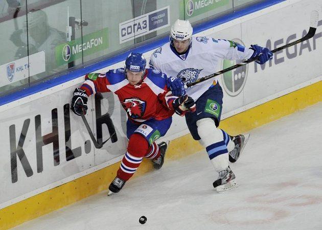 Útočník Petr Vrána (vlevo) z Lva Praha se snaží podél mantinelu uniknout Romanu Savčenkovi z Astany