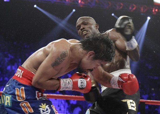 """Hvězdný boxer Manny Pacquiao (vlevo) """"trpí"""" pod údery novopečeného šampióna Američana Timothy Bradleyho"""