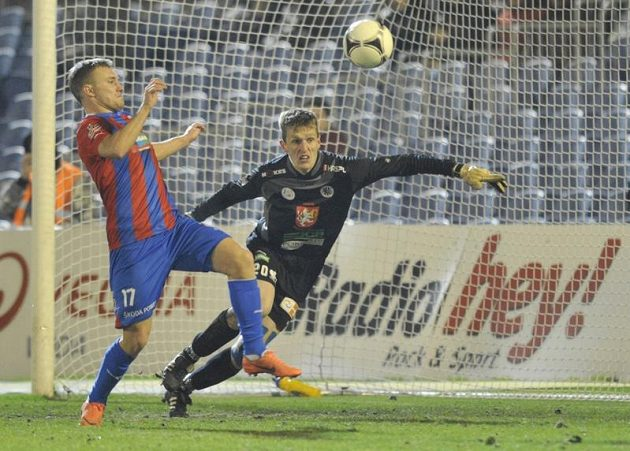 Plzeňský útočník Jakub Hora se snaží odehrát míč před hradeckým brankářem Jiřím Lindrem.