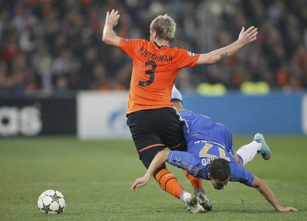 Tomáš Hübschman ze Šachtaru Doněck padá po faulu Edena Hazarda z Chelsea ve třetím kole Ligy mistrů.