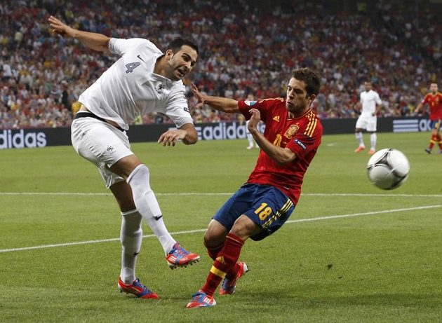 Španěl Jordi Alba (vpravo) se snaží zblokovat střelu Francouze Adila Ramiho