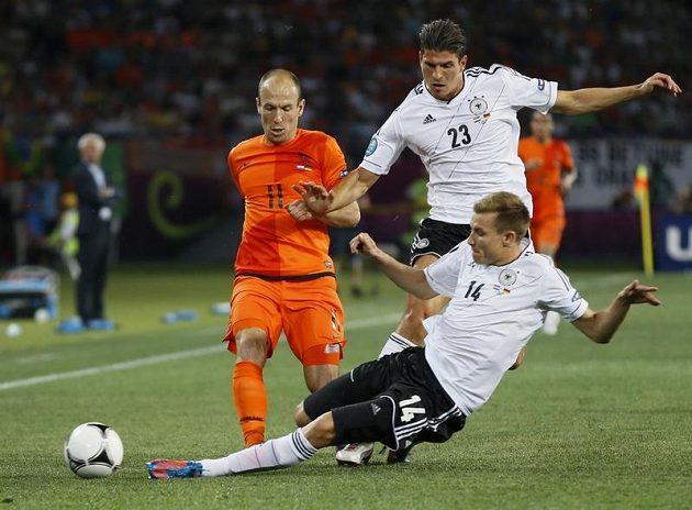 Německý zadák Holger Badstuber (ve skluzu) zastavuje ve spolupráci s Mariem Gomezem klubového spoluhráče z Bayernu v nizozemském dresu Arjena Robbena
