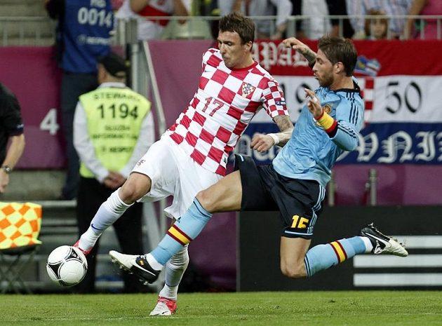 Sergio Ramos ze Španělska (vpravo) skáče do přihrávky Maria Mandžukiče z Chorvatska. S míčem však zasáhl také chorvatského útočníka.