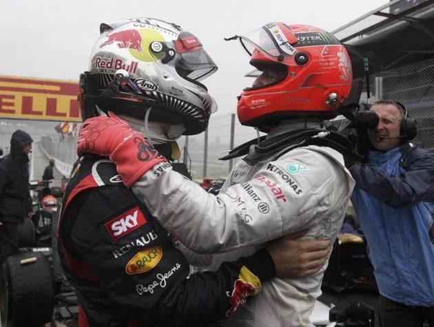 Michael Schumacher (vpravo) gratuluje Sebastianovi Vettelovi.