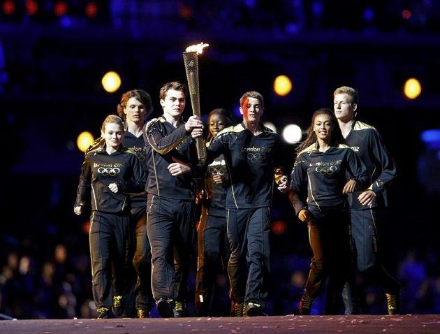 Mladí sportovci nesou olympijský oheň na stadiónu.