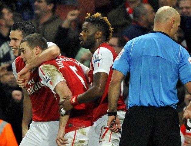Fotbalisté Arsenalu Robin van Persie (vlevo) a Alex Song (druhý zprava) se radují se střelcem gólu Thomasem Vermaelenem.