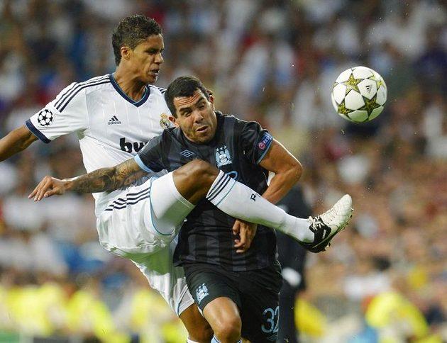 Raphael Varane z Realu Madrid (vlevo) těsně brání Carlose Téveze z Manchesteru City