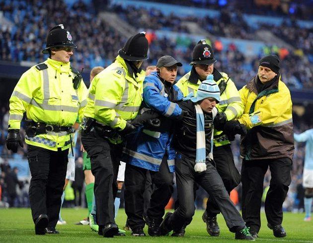 Policie odvádí fanouška Manchesteru City, který vnikl na hřiště.