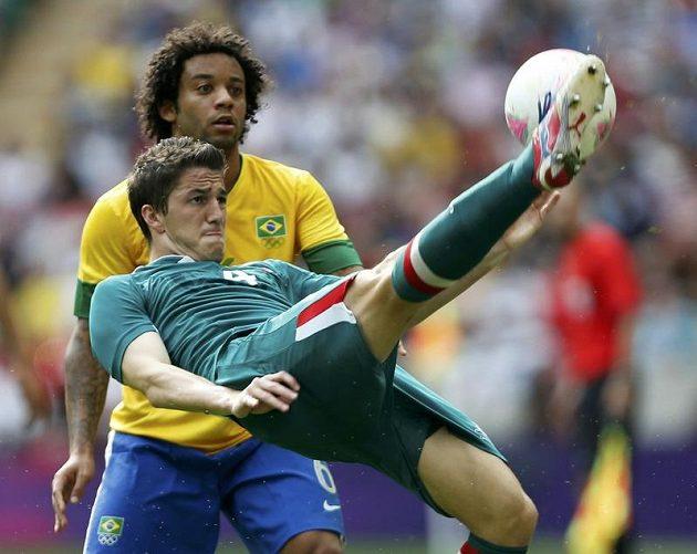 Mexičan Hiram Mier (vpředu) odkopává míč před Brazilcem Marcelem.