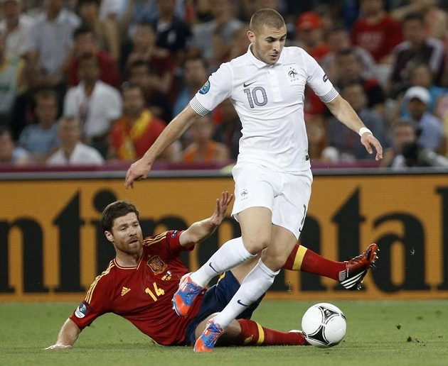 Francouzský snajpr Karim Benzema (č. 10) v souboji se střelcem španělských gólů Xabim Alonsem