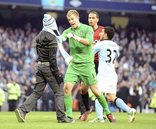 Brankář Manchesteru City Joe Hart zastavuje fanouška, který si chtěl vyšlápnout na Ria Ferdinanda z Manchesteru United, jehož drží Carlos Tevez.