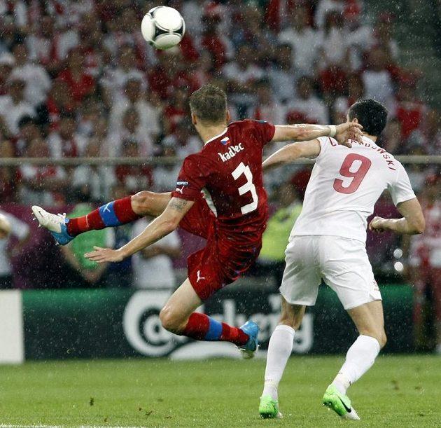 Michal Kadlec akrobatickým zákrokem odkopává míč před Polákem Leawandowskim.