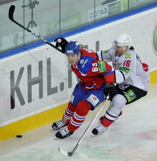 Ondřej Němec z týmu Lev Praha (vlevo) v souboji o puk s Randym Robitaillem z Novokuzněcku.