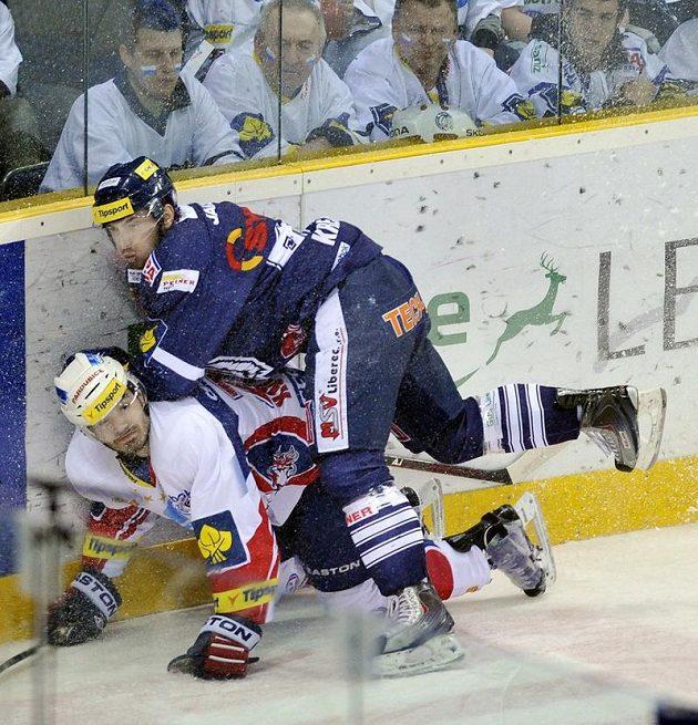 Lukáš Krejčí z Liberce (nahoře) tlačí k ledu pardubického Jana Koláře v semifinále extraligy.